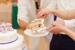Slice of Cake. Bride and groom holding slice of wedding cake Stock Images