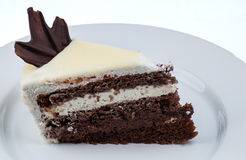Slice of cake with chocolate and whipped cream with white chocolate topping on a white plate stock images