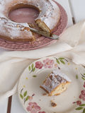 Slice of cake Ciambellone with crumbs on ceramic plate painted with floral motifs, cloth towel and mother of pearl fragments. Stock Photos