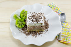 A slice of cake with kiwi garnish on a plate Royalty Free Stock Images