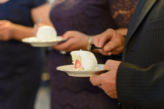 Slice of Cake on Plate. Guest holding plate with wedding cake Royalty Free Stock Images