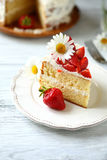 Slice of cake with strawberries on a white plate Stock Images