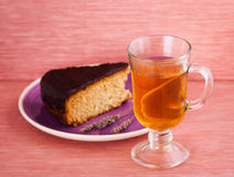 Slice of cake with tea. Slice of cake on the plate with tea Royalty Free Stock Images