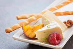 Slice camembert cheese with grilled peach, fresh raspberries and. Thyme, close up Royalty Free Stock Image