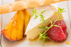 Slice camembert cheese with grilled peach, fresh raspberries and. Fresh thyme, close up Stock Images