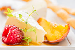 Slice camembert cheese with grilled peach, fresh raspberries and. Fresh thyme, close up Royalty Free Stock Photos
