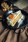 Slice of carrot cake with cream cheese and walnuts. The restaurant or cafe atmosphere. Vintage Royalty Free Stock Images