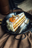Slice of carrot cake with cream cheese and walnuts. The restaurant or cafe atmosphere. Vintage Royalty Free Stock Photos