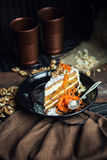 Slice of carrot cake with cream cheese and walnuts. The restaurant or cafe atmosphere. Vintage Stock Images