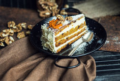 Slice of carrot cake with cream cheese and walnuts. The restaurant or cafe atmosphere. Vintage Stock Photography