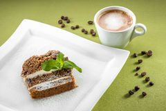 A slice of carrot cake on green background with coffee Stock Photo