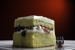 Slice of Chantilly cake. A slice of Chantilly Cake lit against a red background Royalty Free Stock Photos