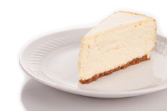 A slice of cheescake on a white plate royalty free stock image