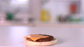 Slice of cheese falling on bun burger in kitchen stock video
