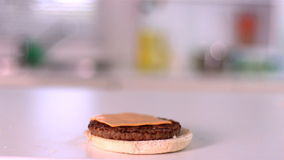 Slice of cheese falling on bun burger in the kitchen stock footage