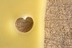 Slice of cheese with a hole in the shape of a heart on a wooden. Cutting board Royalty Free Stock Images