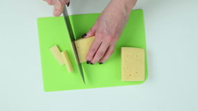 Slice cheese into pieces stock video footage