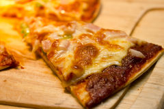 Slice cheese of pizza is lifted from the pan Stock Photo