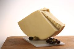 Slice of cheese wheel next to some olives.  Royalty Free Stock Image