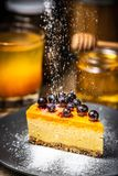 Slice of cheesecake with berries on a blue plate. Sugar snow. Powdered sugar stock photos