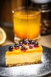 Slice of cheesecake with berries on a blue plate. Thick dripping honey. Powdered sugar stock photos