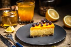 A slice of cheesecake with berries on a dark plate royalty free stock photography