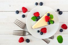 Cheesecake with blueberries and raspberries, top view over white wood Stock Photography