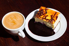 Slice cheesecake with blueberry jam and cup of americano coffee Stock Photography