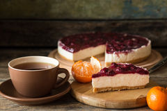 Slice of cheesecake with cherries and cup of tea. Slice of cheesecake with cherries on wooden board, some mandarins and cup of tea Stock Photo