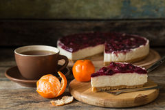 Slice of cheesecake with cherries and cup of tea. Slice of cheesecake with cherries on wooden board, some mandarins and cup of tea Royalty Free Stock Photo