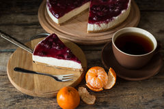 Slice of cheesecake with cherries and cup of tea. Slice of cheesecake with cherries on wooden board, some mandarins and cup of tea Stock Photography