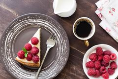 Slice of cheesecake with raspberries and cup of coffee on wood table. Top view Stock Images