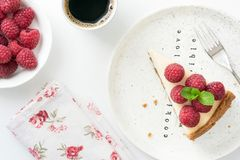 Slice of cheesecake with raspberries on white, table top view royalty free stock photography