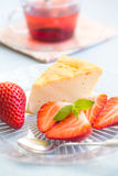 Slice of cheesecake with strawberries. And a cup of tea royalty free stock image