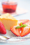 Slice of cheesecake with strawberries. And a cup of tea royalty free stock photography