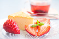 Slice of cheesecake with strawberries. And a cup of tea stock image