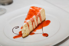 Slice of Cheesecake with Strawberry Sauce and Chocolate Swirl Royalty Free Stock Photo
