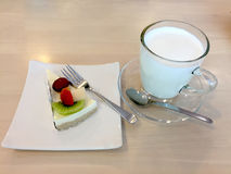 Slice Of Cheesecake Topped With Strawberry, Kiwi, Grap And Cantaloupe Compote On Plate On Wood Table With Dessert Fork And Milk Royalty Free Stock Image