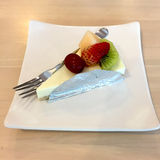 Slice Of Cheesecake Topped With Strawberry, Kiwi, Grap And Cantaloupe Compote On Plate On Wood Table Royalty Free Stock Images