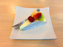 Slice Of Cheesecake Topped With Strawberry, Kiwi, Grap And Cantaloupe Compote On Plate On Wood Table Royalty Free Stock Photography