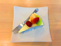 Slice Of Cheesecake Topped With Strawberry, Kiwi, Grap And Cantaloupe Compote On Plate On Wood Table Stock Photo