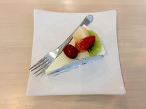 Slice Of Cheesecake Topped With Strawberry, Kiwi, Grap And Cantaloupe Compote On Plate On Wood Table Royalty Free Stock Photos