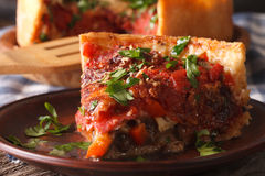 Slice of Chicago deep dish pizza on a plate macro. Horizontal Stock Photos