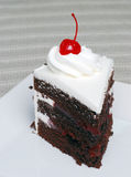 Slice of chocolate black forest cake with a cherry. With a striped tablecloth Royalty Free Stock Photos