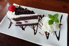 Slice of chocolate black forest cake with a cherry Stock Images