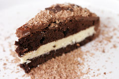 Slice of chocolate cake. Single slice of chocolate cake with scattered topping, white background Stock Images