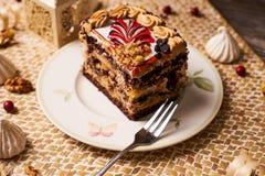 Slice of Chocolate cake with banana, walnut, meringue royalty free stock image