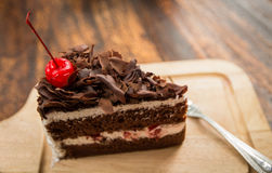 Slice of chocolate cake with cherries topping and frok on wood table. Slice of chocolate cake with cherries topping Stock Photos