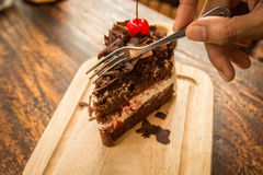 Slice of chocolate cake with cherries topping and frok on wood table. Slice of chocolate cake with cherries topping Stock Photography