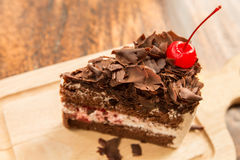 Slice of chocolate cake with cherries topping and frok on wood table. Slice of chocolate cake with cherries topping Stock Photo